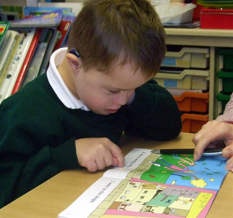 A photograph of a boy with Down syndrome learning to read a book