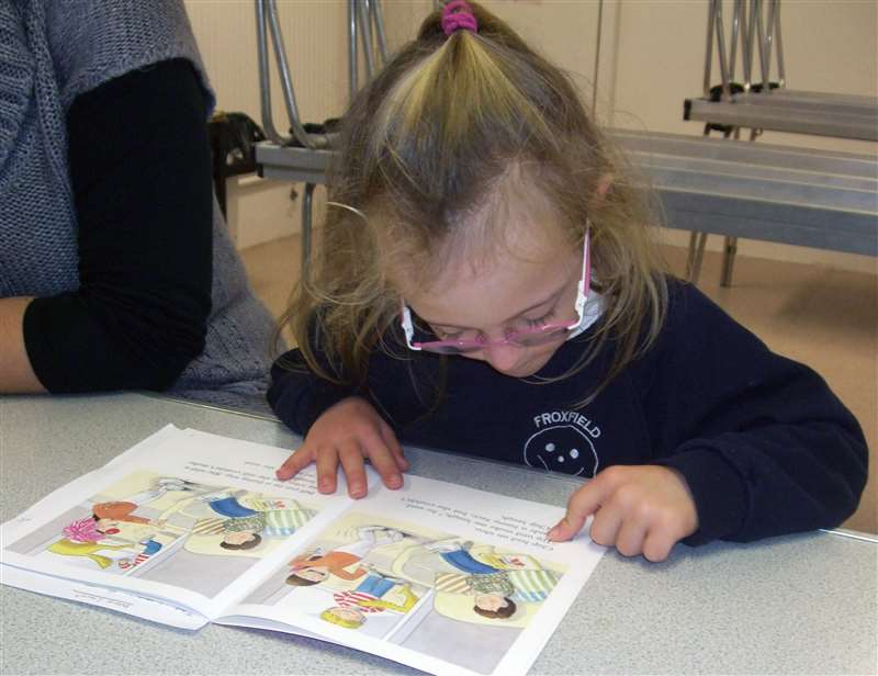 A photograph of a girl with Down syndrome learning to read a book.