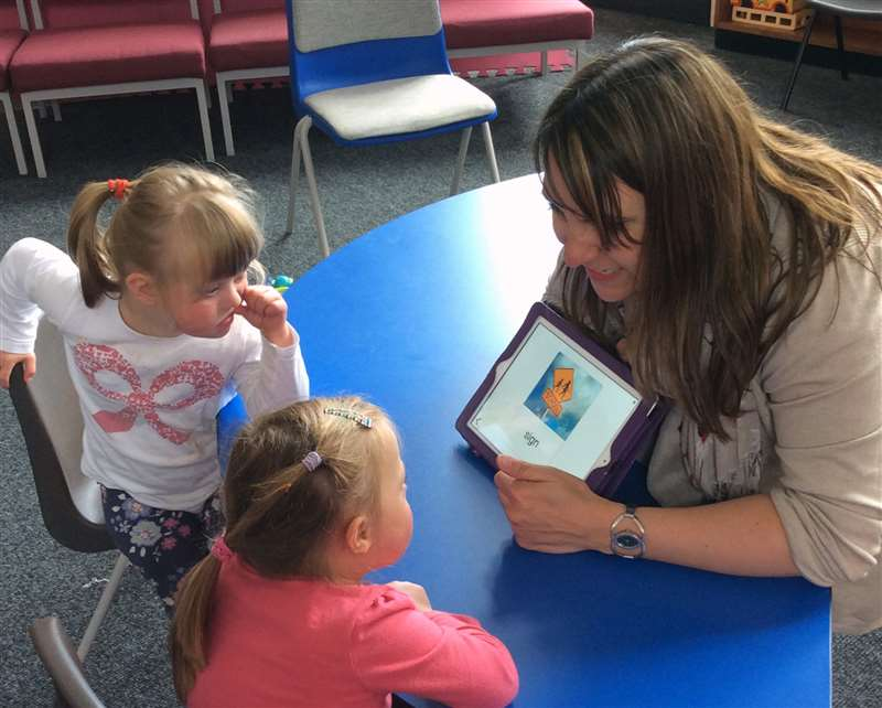 A photograph of a speech pathologist working with children with Down syndrome
